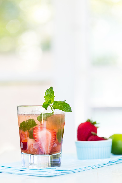 Cocktail glass filled with a cocktail and strawberries, garnished with mint.