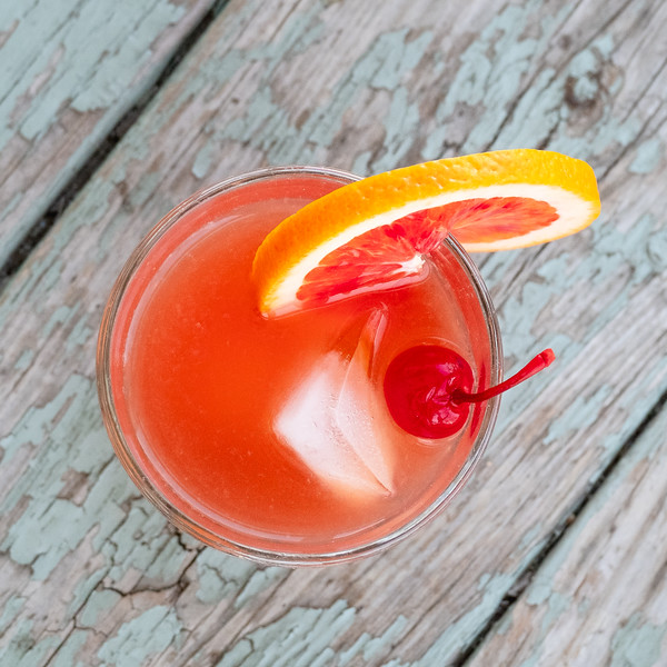 Bright orange cocktail with red cherry and orange slice