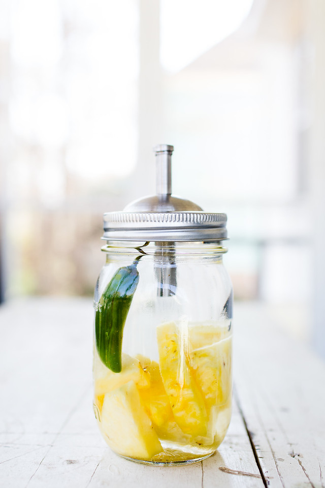 Mason Jar filled with tequila, pineapple and a jalapeño pepper