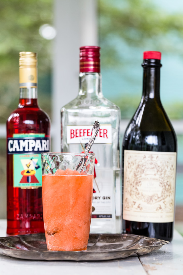 a frozen negroni with a bottle of campari, gin, and vermouth behind it