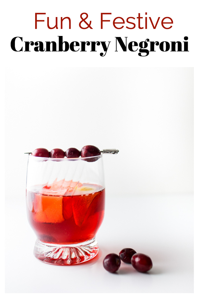 Cocktail glass filled with a red cocktail and garnished with cranberries - text overlay reads Fun & Festive Cranberry Negroni