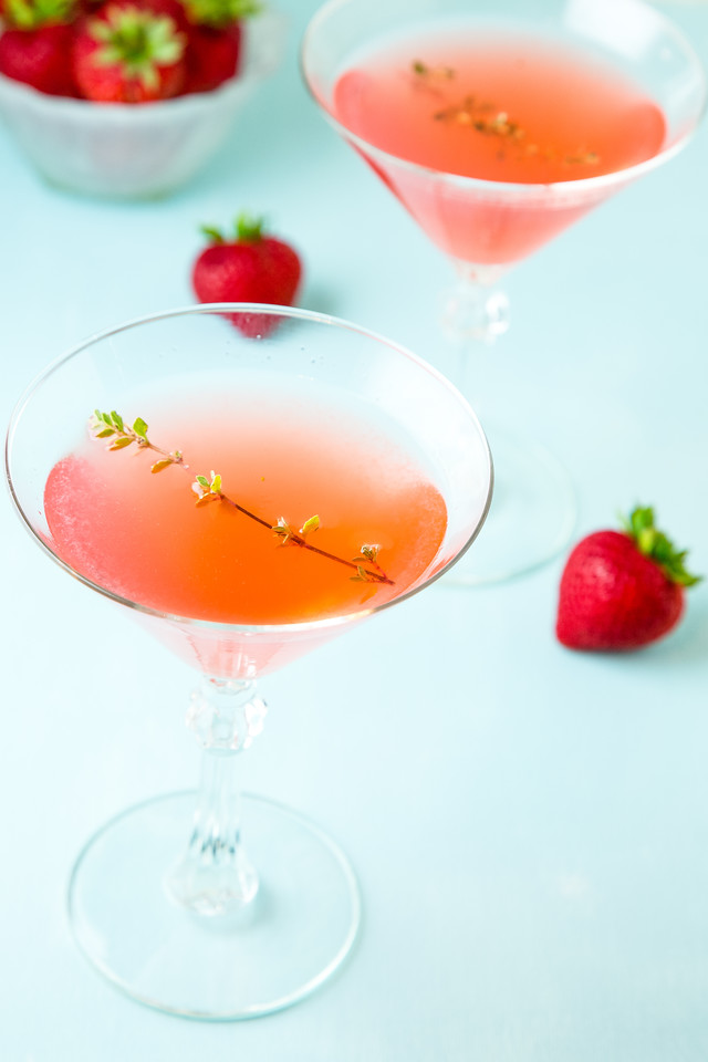 Pink cocktail on blue background with strawberries