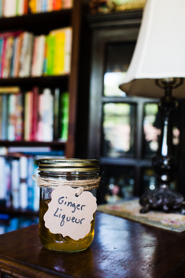 Mason jar with Ginger liqueur label in front of a bookcase.