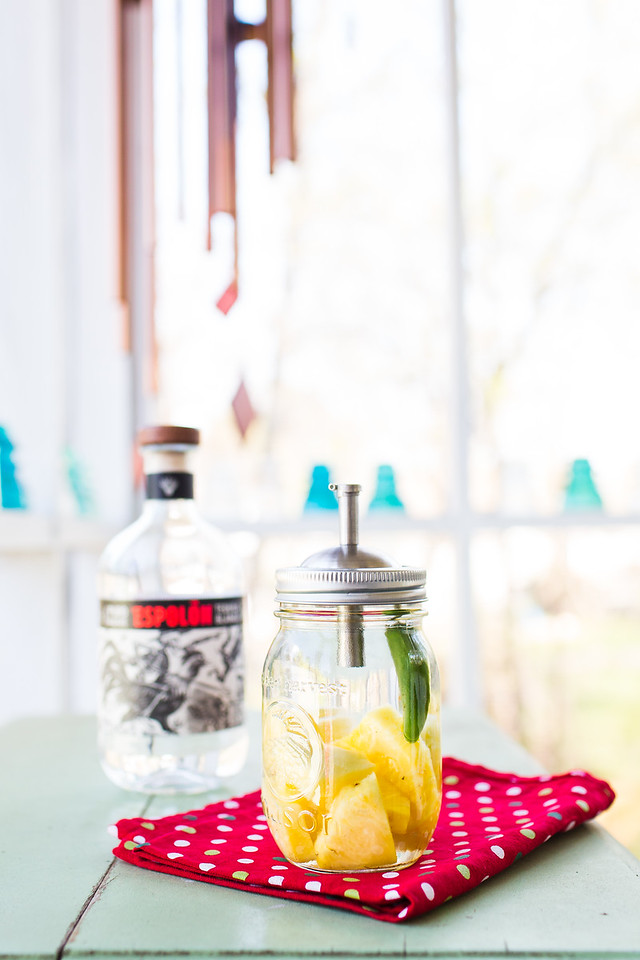 Mason jar filled with tequila, pineapple and jalapeno.