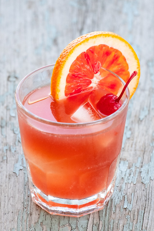Bright orange red cocktail garnished with a cherry and a blood orange slice.
