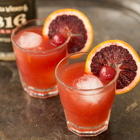 Two glasses of bright red drinks garnished with blood oranges and a cherry.
