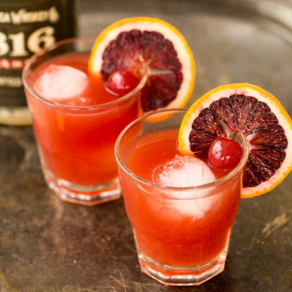 Two deep red orange cocktails with blood oranges and cherry garnishes
