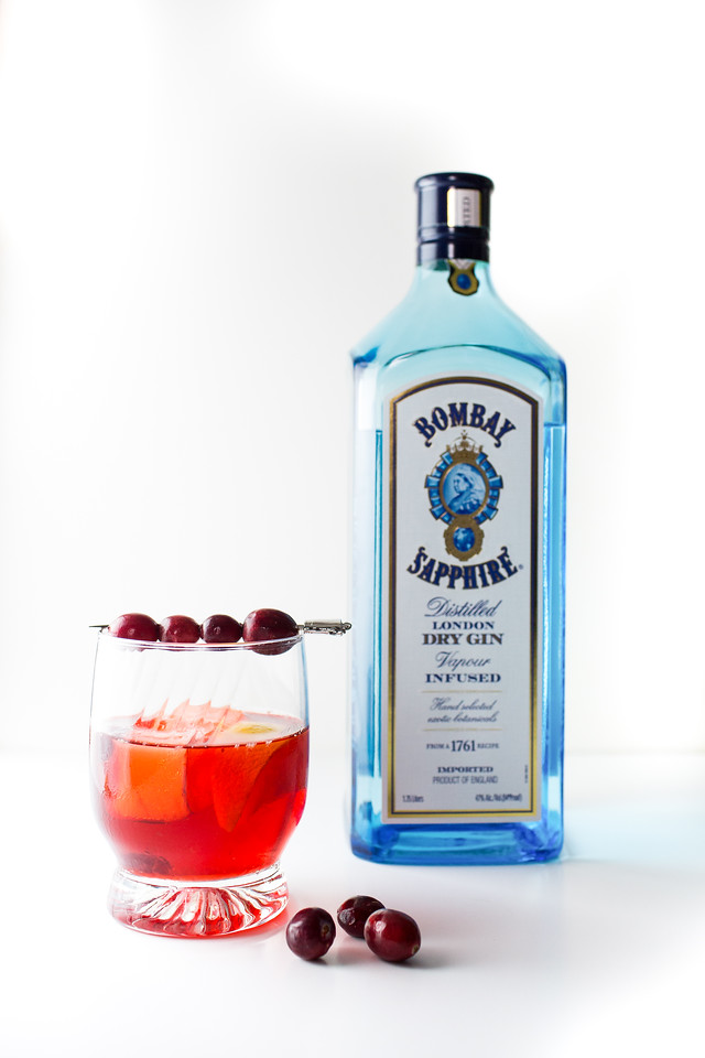 Red cocktail garnished with cranberries in front of a bottle of Bombay Sapphire Gin.
