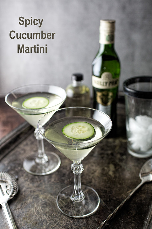 Two Martini glasses with floating cucumber slices and text reading Spicy Gin Martini