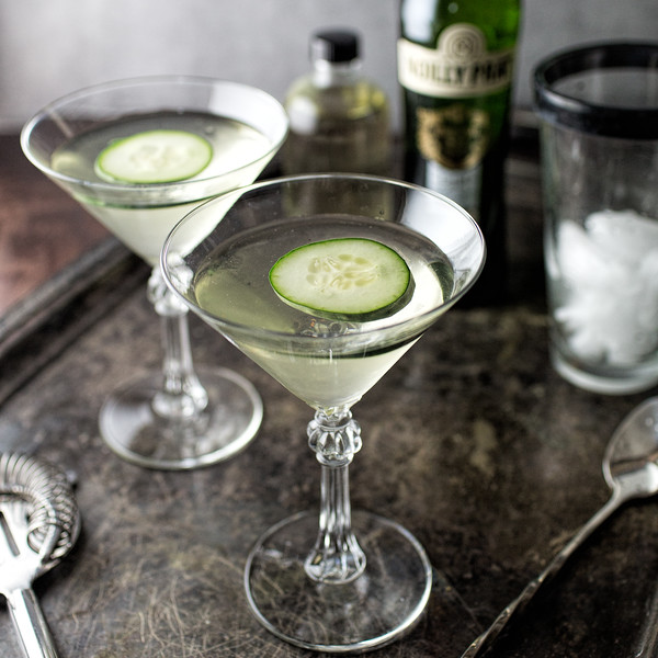 Two martini glasses with pale green liquid and floating cucumber slices - cucumber martini