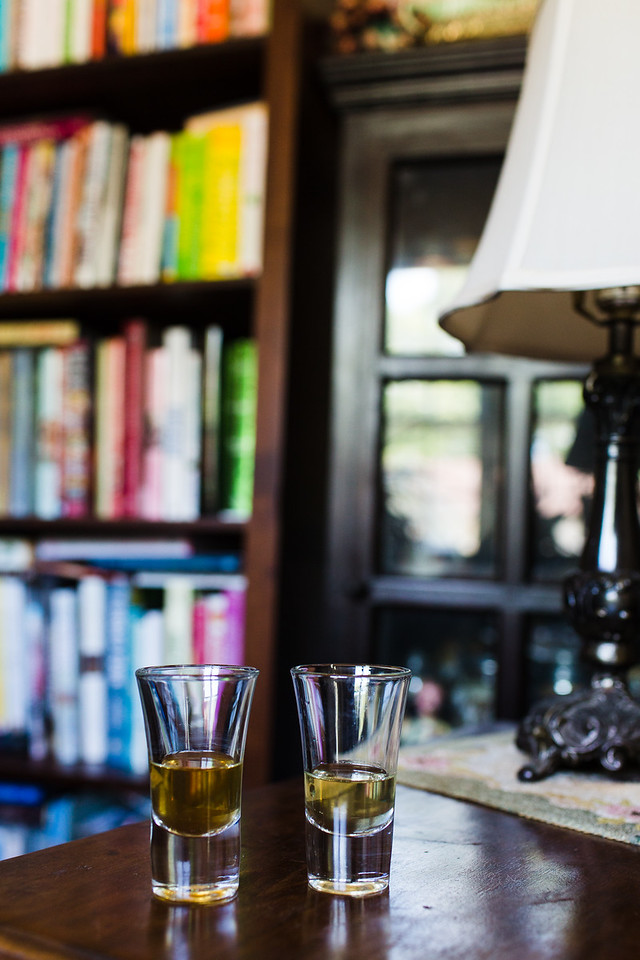 Two shot glasses filled with golden liquid in front of a bookcase.