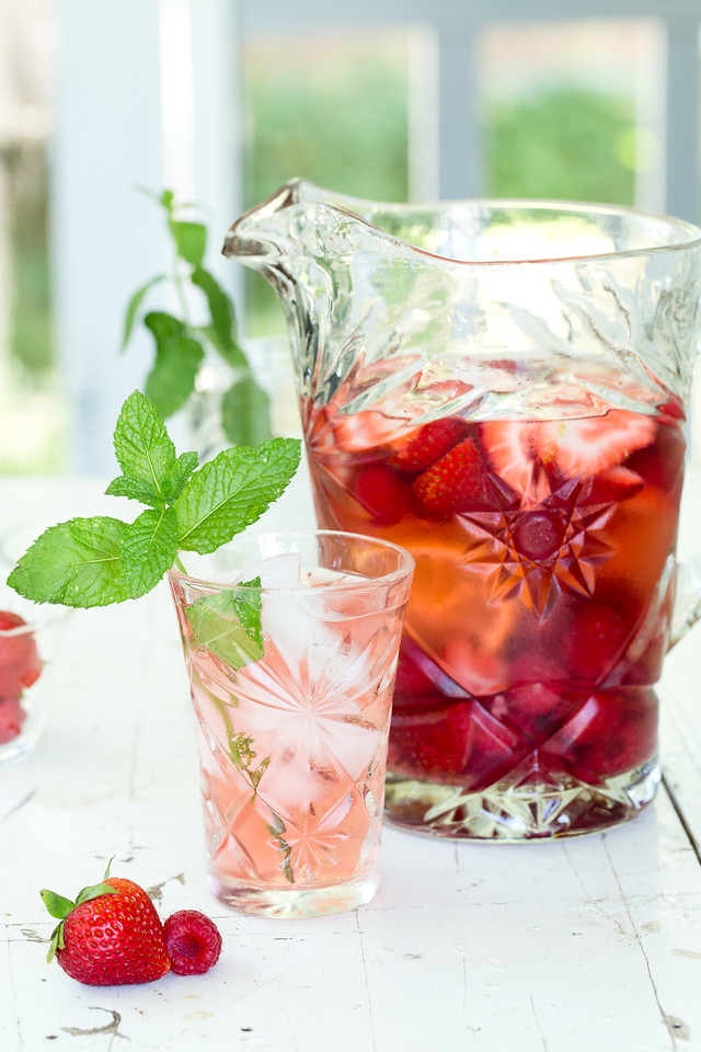 Pitcher of a red liquid with a glass garnished with mint and strawberries
