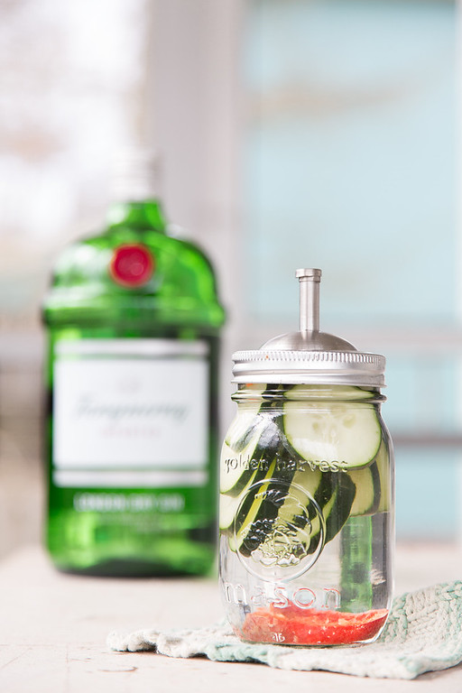 Mason jar with cucumbers and pepper in front of a bottle of gin