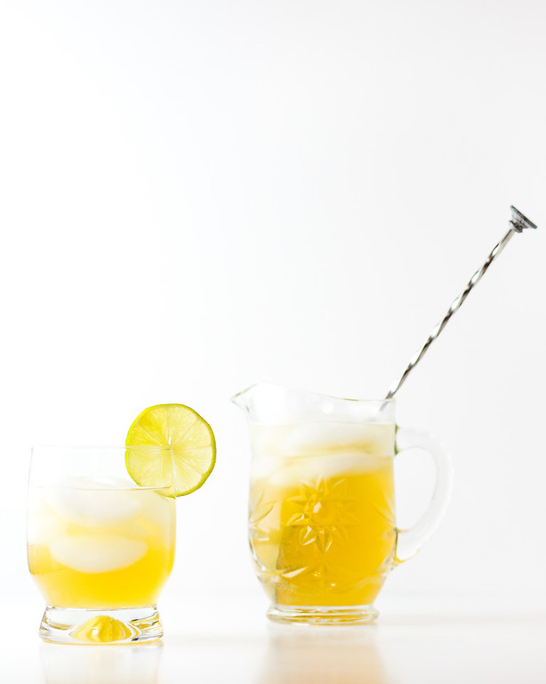 Lemon yellow cocktail with small pitcher garnished with a lemon slice