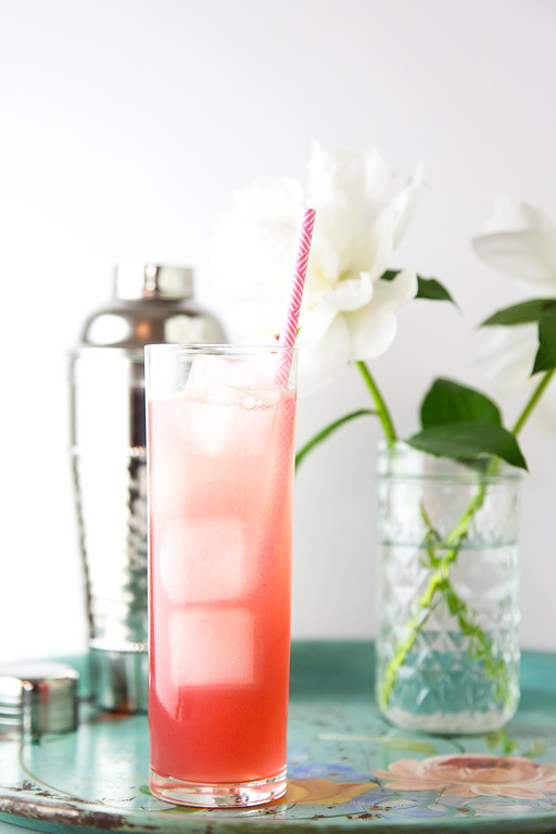 Pretty pink cocktail with a straw in front of a vase of flowers.