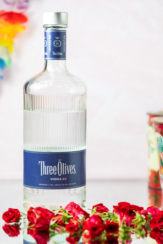 A bottle of vodka with roses in front of it.