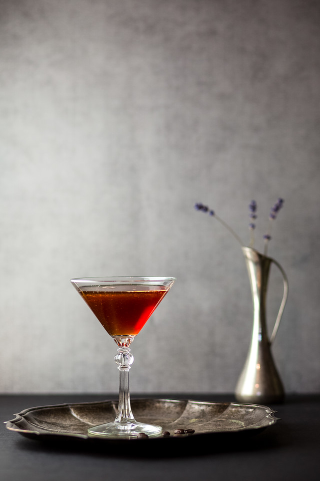 Reddish brown cocktail in a martini glass with a silver tray and vase behind it.