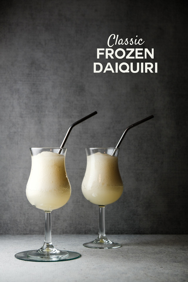 Two glasses of a frozen daiquiri on a gray background with text overlay reading Classic Frozen Daiquiri