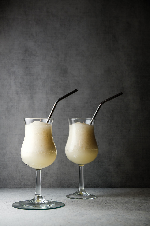 two glasses of frozen daiquiri on a gray background