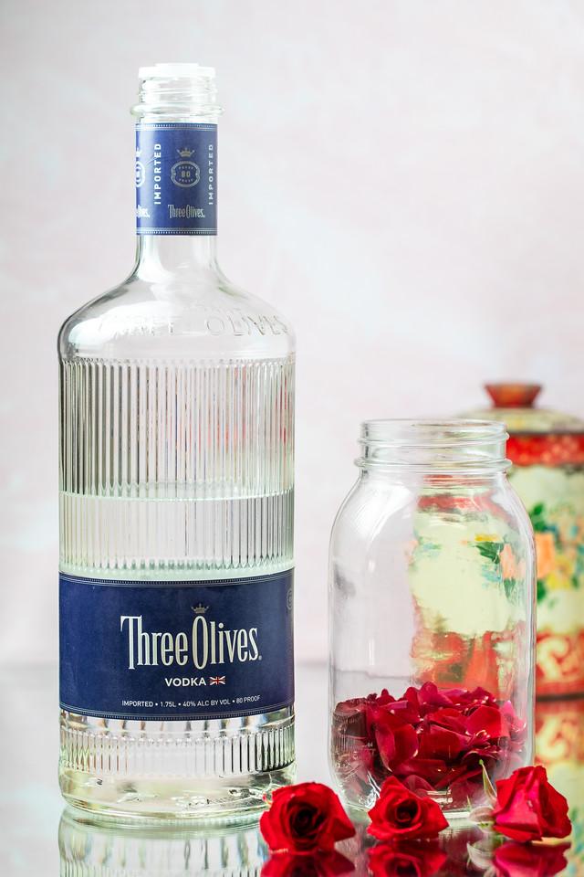 Bottle of vodka with rose petals inside a jar.