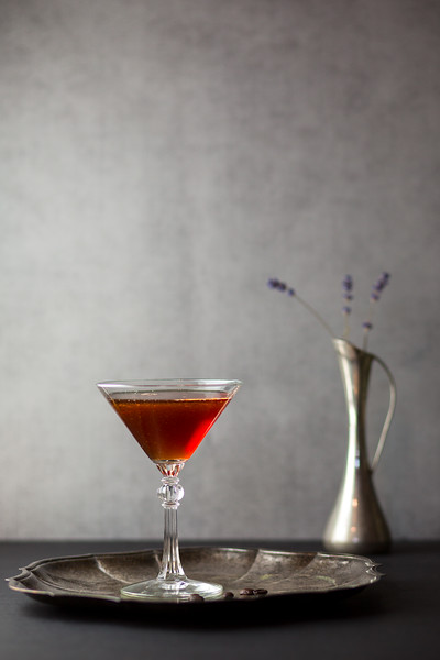 Red cocktail with a silver vase behind it.