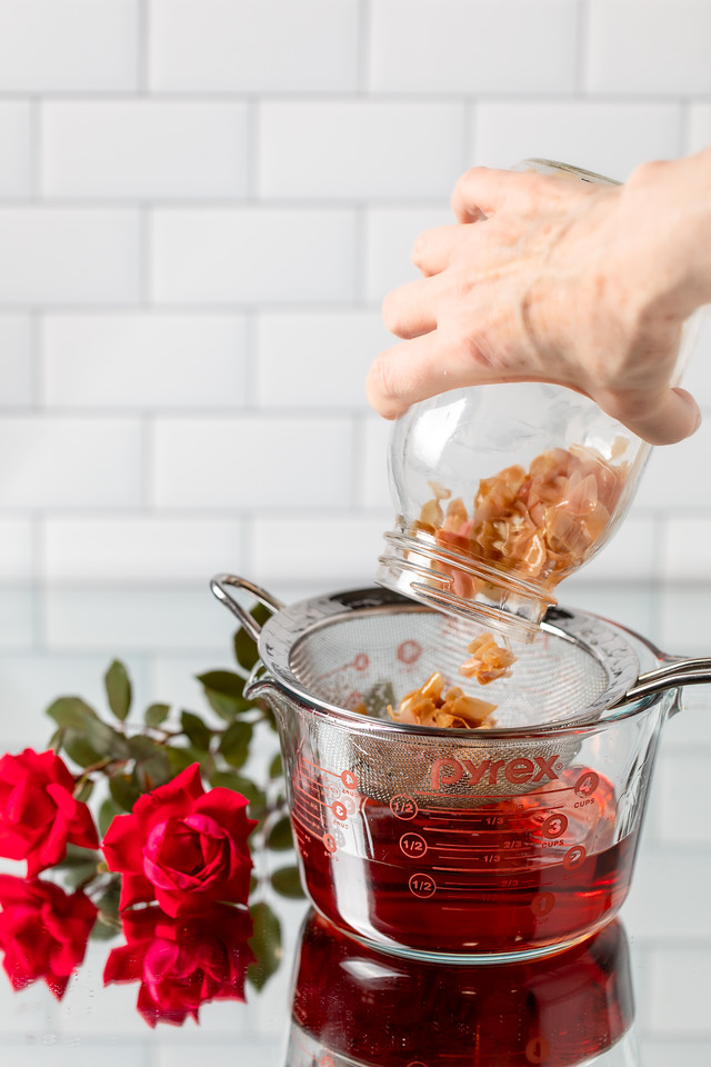 Photo showing rose petals being strained out of vodka.