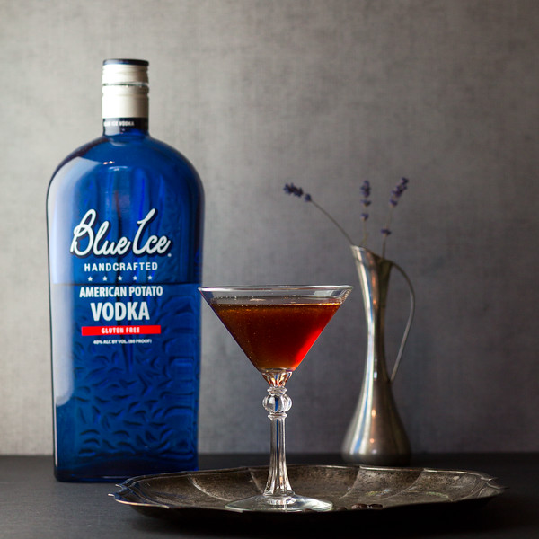 Bottle of blue ice vodka and a martini glass filled with a brown cocktail