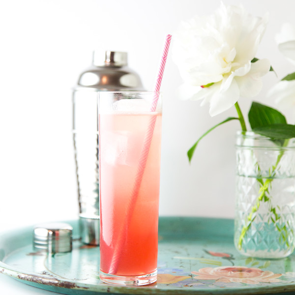 Pretty pink cocktail in a tall glass with a pink and white straw.