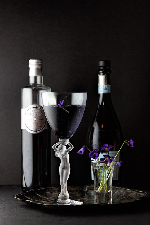 Dark purple cocktail with two bottles in the background and a small vase of violets.