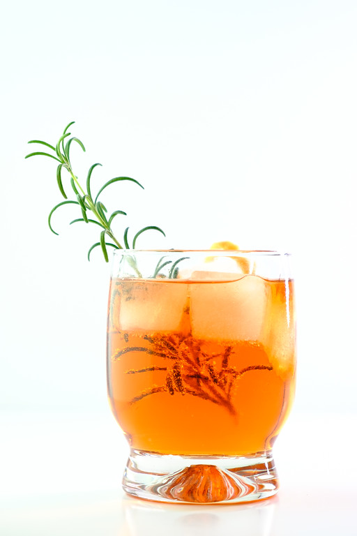 Glass with orange cocktail and rosemary sprig