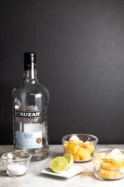 Bottle of rum, sugar, lime, mango chunks and pineapple chunks.