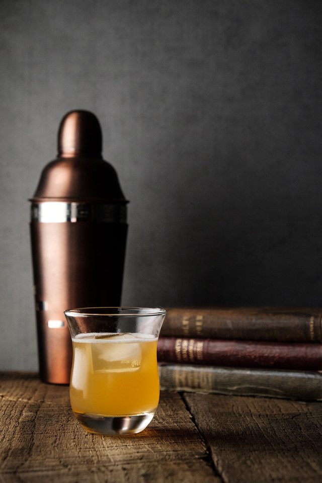 Glass filled with dark orange liquid, vintage books and a copper colored cocktail shaker in a dark and moody photo