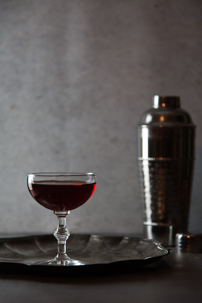 Deep red cocktail with silver cocktail shaker