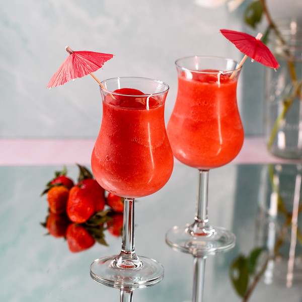 Two bright red cocktails in hurricane glasses, garnished with cocktail umbrellas.