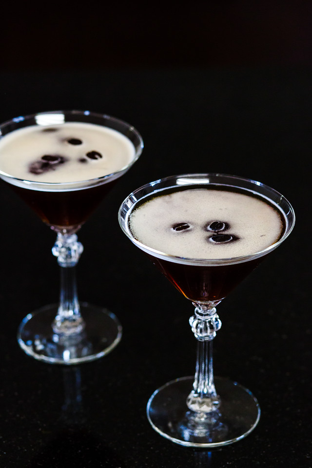 Two martini glasses filled with a dark espresso martini and topped with coffee beans.