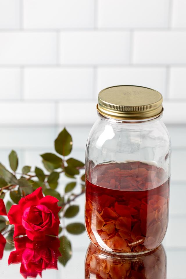 Bottle of pale rose petals in vodka in a jar.