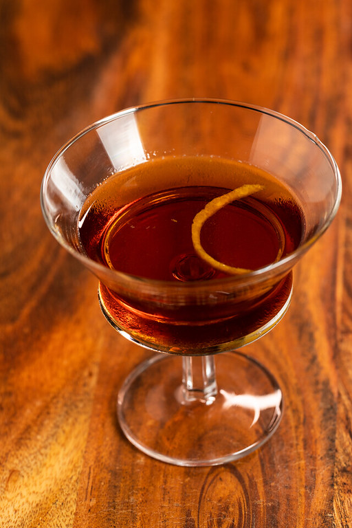 A brown cocktail with an orange twist on a wooden table.
