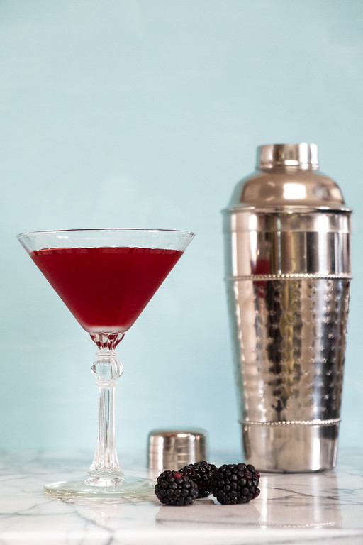 Dark purple blackberry martini in front of a cocktail shaker
