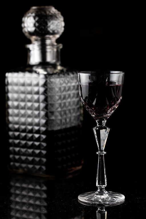 Glass with dark red liquid and a decanter.