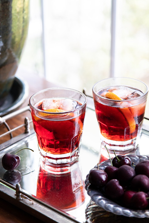 Two glasses filled with a reddish cocktail with a bowl of cherries.