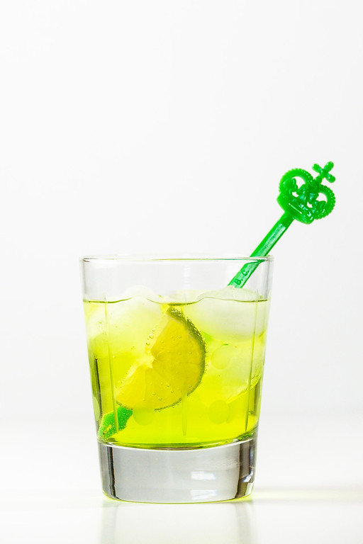 Bright green cocktail with a green cocktail stirrer.
