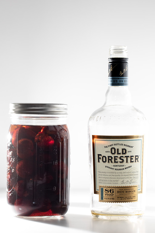 Cherries in a jar with bourbon and an empty bourbon bottle next to it.