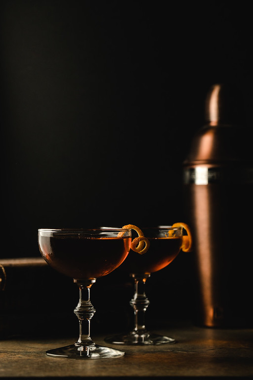 Two coupe glasses filled with a dark red cocktail.