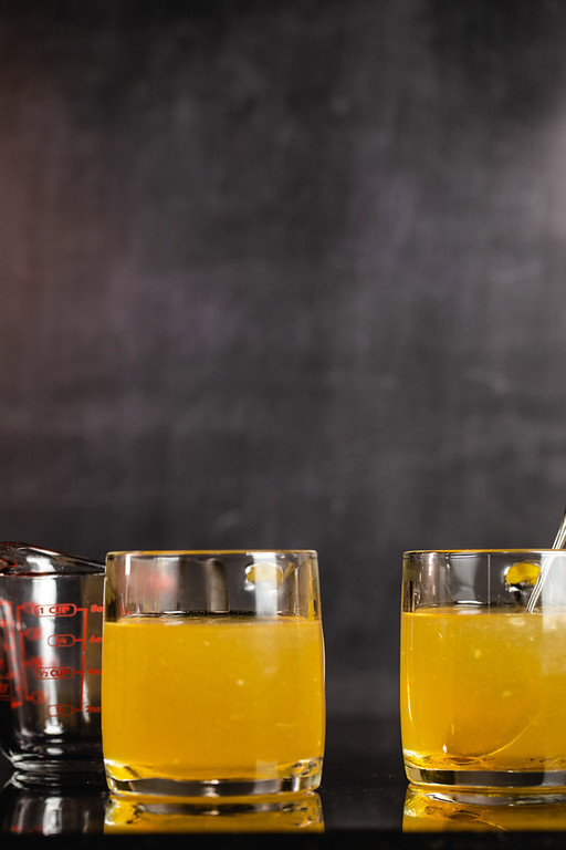 Two glass mugs with bright orange liquid hot toddy.