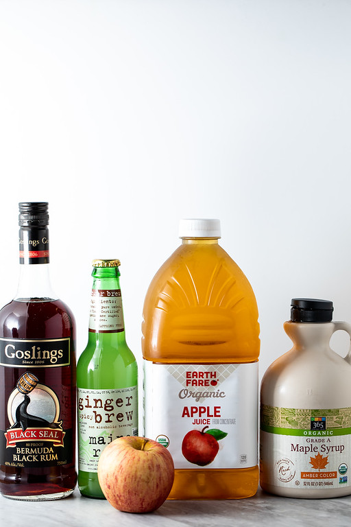 Dark rum, ginger beer, apple juice, maple syrup and an apple - ingredients to make an Apple Maple Dark and Stormy.