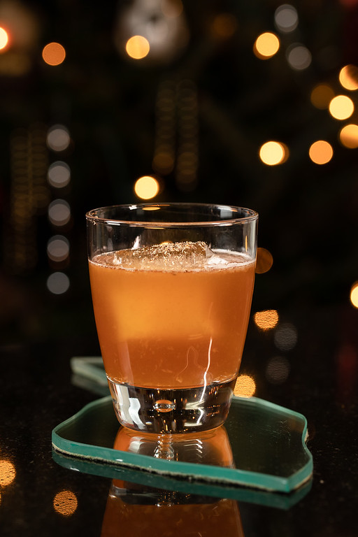 Orange cocktail with Christmas lights in the background.