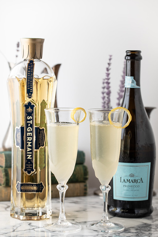 Two glasses of French 77 cocktail with a bottle of St. Germain and prosecco.