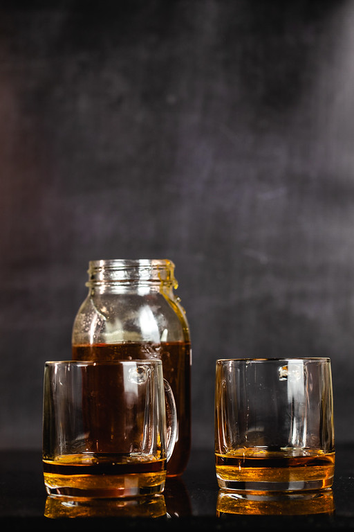 Opened jar of honey and honey and bourbon in two glass mugs.