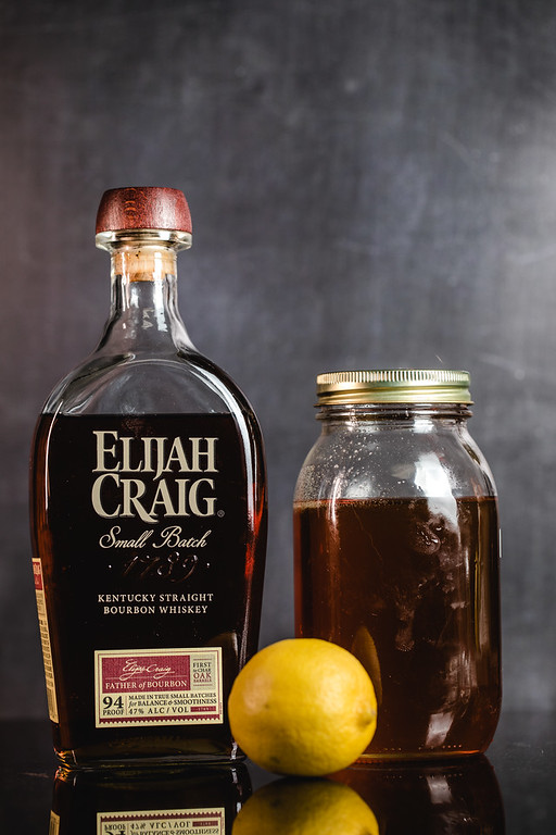 Bottle of bourbon, jar of honey, and a lemon to make a hot toddy.