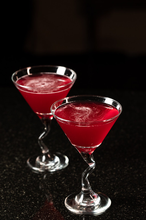 Two martini glasses filled with bright red cosmo martini.